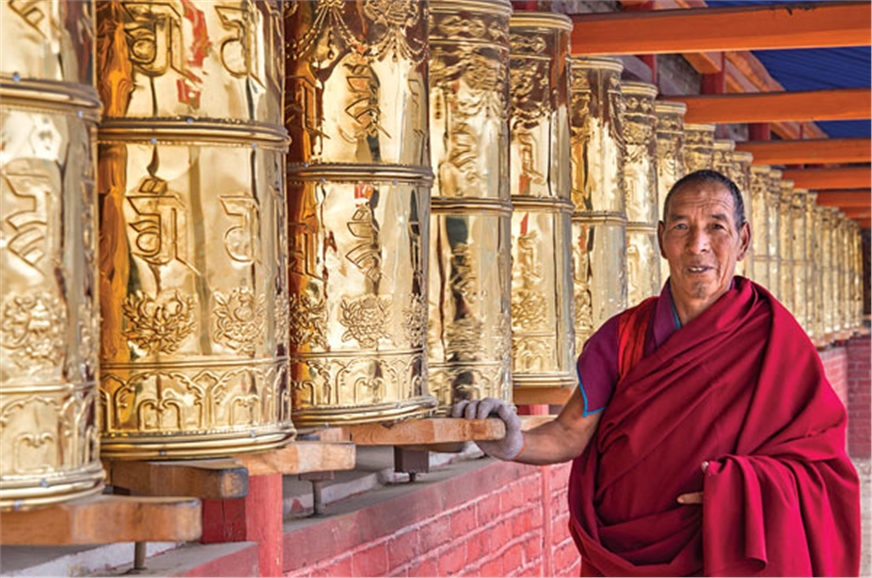 A monk by the prayer wheels at a Tibetan monastery.