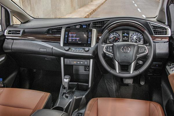 Classy mix of black, dark wood and tan. Dashboard stylistically 'opens' up to reveal instrumentation.
