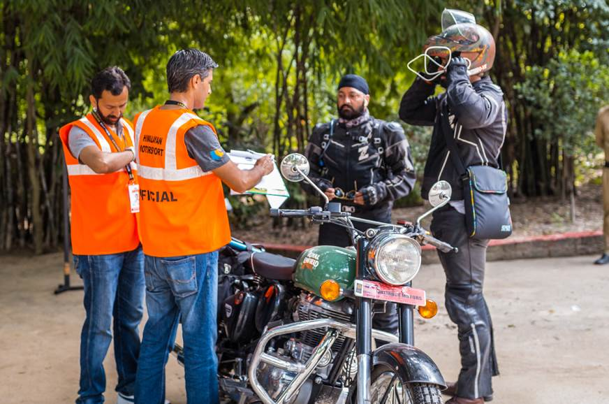 Rally marshals scrutinize bikes and riding gear before th...