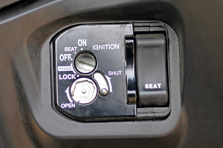 Honda Grazia's ignition with the seat release button.