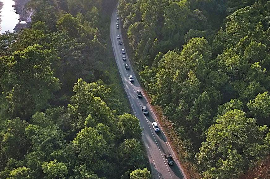 The convoy snakes through narrow mountain roads.
