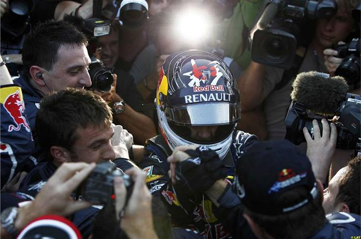 Vettel is swamped by his jubilant Red Bull team immediately after the race in Japan.