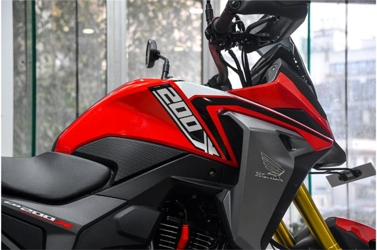 The semi-fairing flows neatly into the fuel-tank, and the CB200X also gets faux radiator shrouds.